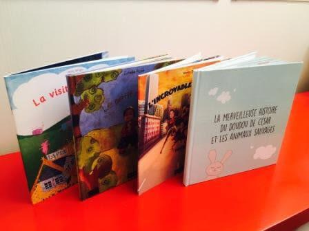 quatre livres personnalisés colorés posés sur une table rouge