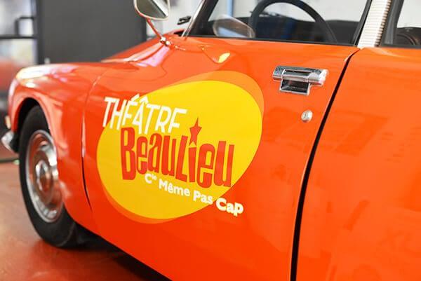 Voiture vintage orange avec logo du Théâtre Beaulieu sur la portière