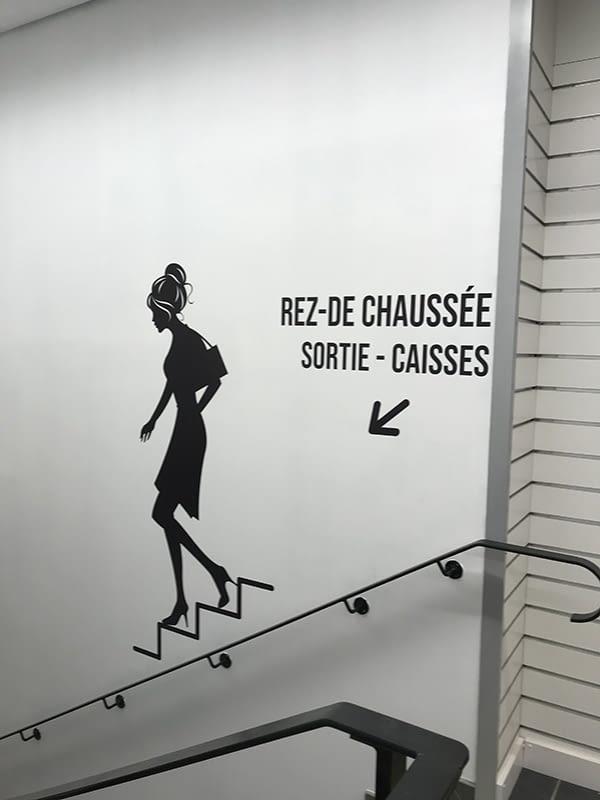 Signalétique directionnelle noir sur mur blanc avec dessin de femme descendant des escaliers