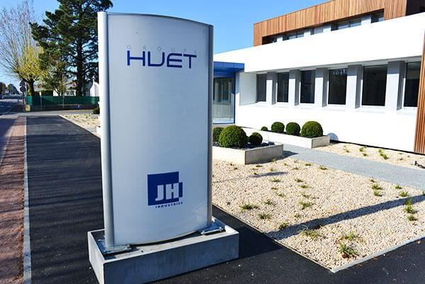 Totem extérieur blanc et bleu avec logo Huet devant bâtiment design