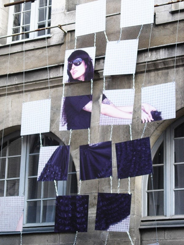 Visuel déstructuré avec photo de femme suspendu sur un mur en pierre